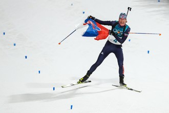 Уроженка России Анастасия Кузьмина на финише масс-старта по биатлону с флагом Словакии