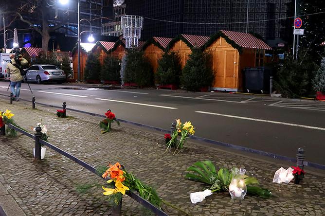 Цветы и свечи рядом с рождественской ярмаркой на площади Брайтшайдплац в Берлине, 20 декабря 2016 года
