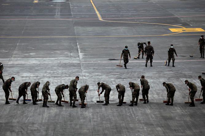 Солдаты подметают асфальт в аэропорту Ла-Аурора