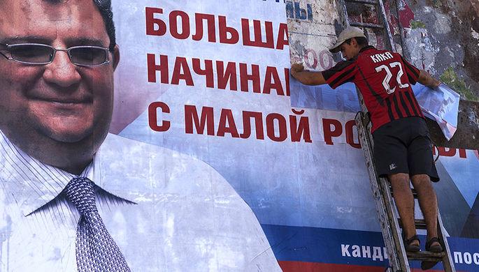 Рабочий расклеивает в Донецке предвыборный плакат кандидата на пост главы города Игоря Мартынова
