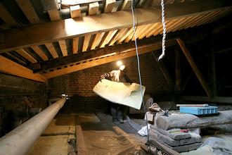 Рабочий утепляет чердак многоэтажного дома