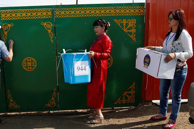 Члены избирательной комиссии несут урну для голосования по открепительным удостоверениям в один из домов в Монголии