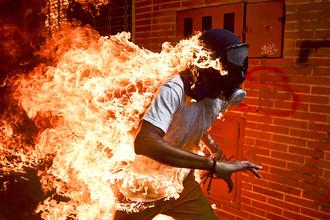 Один из протестующих против президента Венесуэлы Николаса Мадуро оказался охвачен огнем после столкновений с полицией.