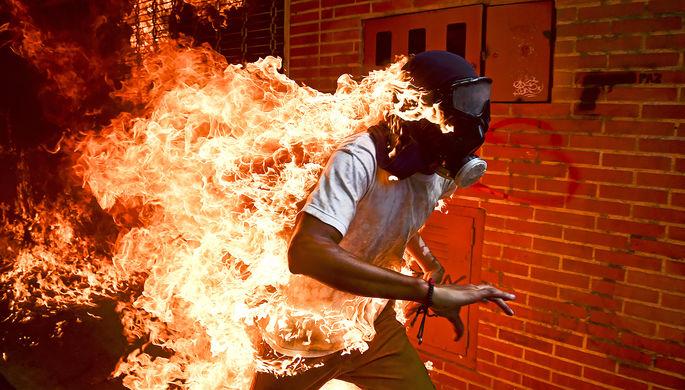 Один из протестующих против президента Венесуэлы Николаса Мадуро оказался охвачен огнем после...