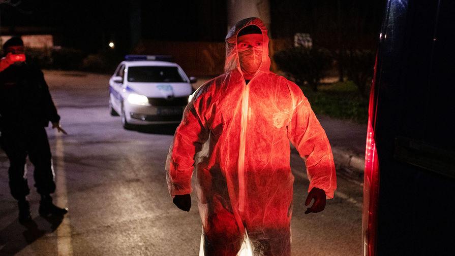 Сотрудник сербской полиции в защитном костюме около инфекционной больницы в Белграде, 17 марта 2020 года