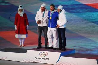 Российские лыжники Андрей Ларьков и Александр Большунов на церемонии закрытия Игр рядом с финном Ийво Нисканеном