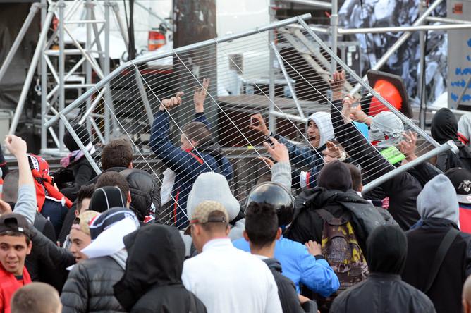 Футбольные хулиганы кидают элементы металлического заграждения в сотрудников полиции