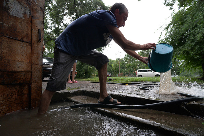 Мужчина вычерпывает воду из подъезда на затопленной улице Уссурийска