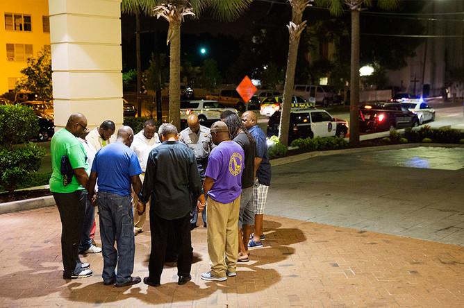 Горожане молятся около афроамериканской церкви, где произошло массовое убийство