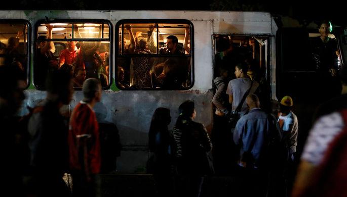 Люди около автобуса во время отключения электричества в Каракасе, 7 марта 2019 года