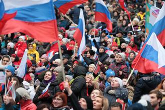 Посетители перед началом митинг-концерта «Россия объединяет!» на большой спортивной арене «Лужники» в Москве.