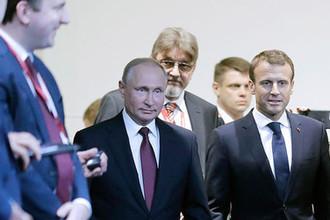 Президент Франции Эммануэль Макрон и президент РФ Владимир Путин (справа налево) во время бизнес-диалога «Россия – Франция» в рамках XXII Петербургского международного экономического форума, 25 мая 2018 года