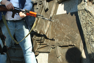 Фрагмент барельефа на памятнике Михаилу Калашникову и представитель общественной организации с автоматом АК-47 в центре Москвы, 22 сентября 2017 года