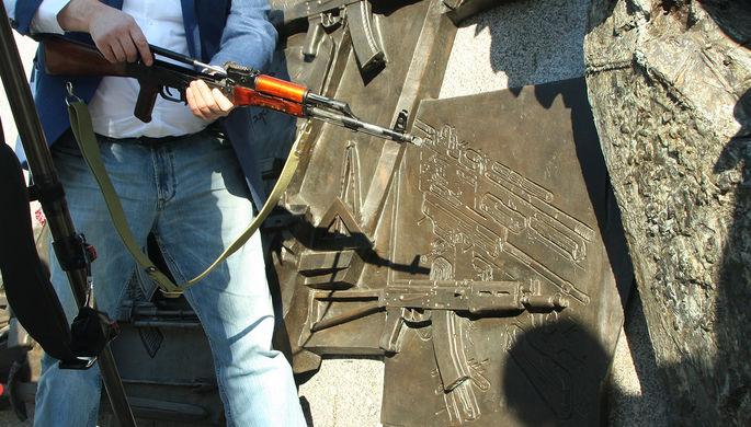 Фрагмент барельефа на памятнике Михаилу Калашникову и представитель общественной организации с...