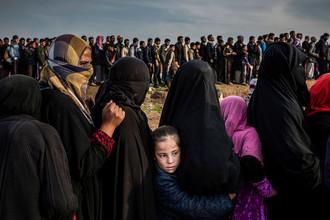 Оставшиеся в Мосуле (Ирак) гражданские лица стоят в длинной очереди за гуманитарной помощью.