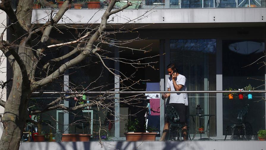 Мужчина стоит на балконе многоквартирного дома в одном из районов Лондона, 24 марта 2020 года