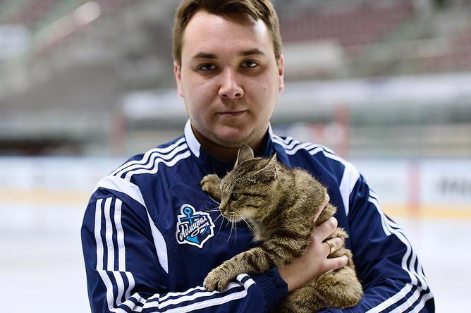 Сотрудник хоккейного клуба «Адмирал» Михаил Быков держит в руках кошку, ставшую талисманом хоккейного клуба «Адмирал»
