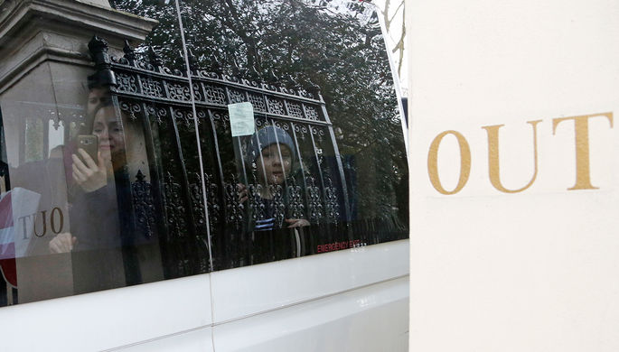 Микроавтобус с дипломатами и их семьями во время выезда с территории российского посольства в...