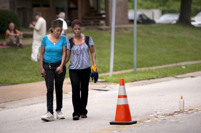 Женщины держат друг друга за руку, осматривая место, где был застрелен полицией Майкл Браун
