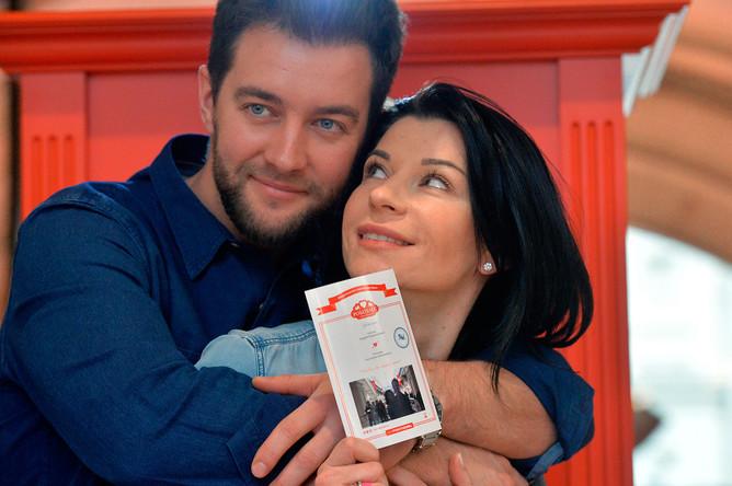 Актриса Екатерина Волкова с супругом Андреем Карповым со свидетельством о виртуальном браке у «Робозагса» в ГУМе