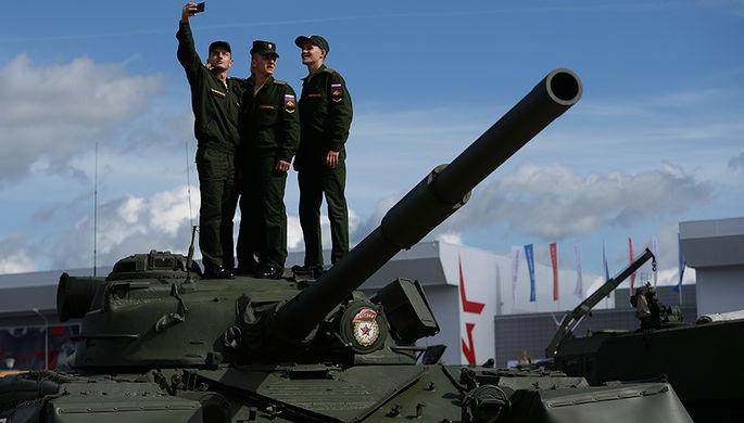 Военнослужащие фотографируются на фоне образцов военной техники в открытой экспозиции на...