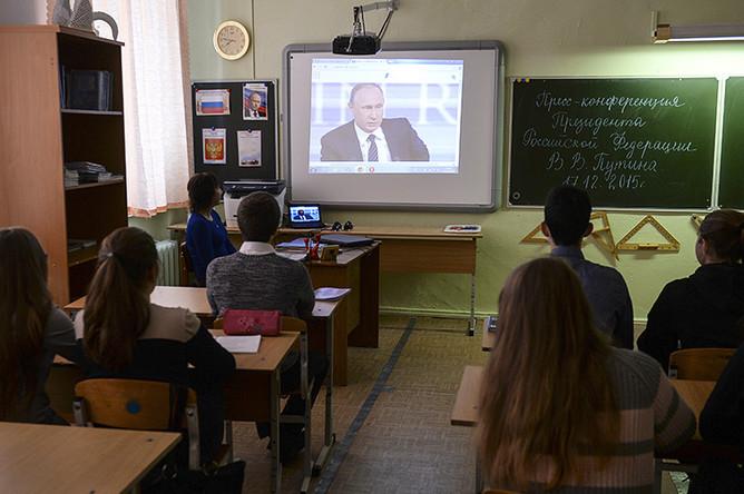 Ученики Калиновской средней школы Свердловской области смотрят телетрансляцию одиннадцатой большой ежегодной пресс-конференции президента России Владимира Путина на уроке обществознания