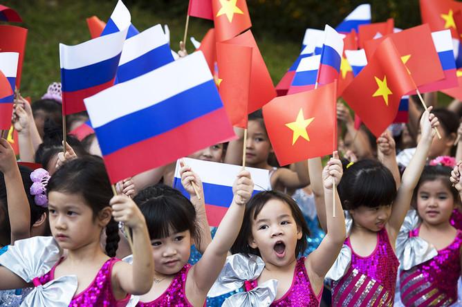Дети с флагами России и Вьетнама на церемонии официальной встречи президента России на площади перед Президентским дворцом в Ханое