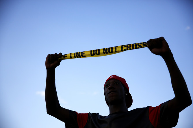 Участник протеста держит полицейскую ленту