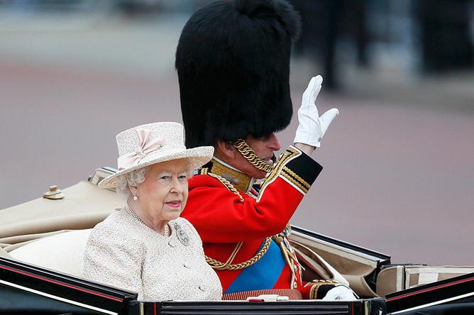 Королева Великобритании Елизавета и принц Филипп возвращаются в Букингемский дворец в карете после посещения церемонии