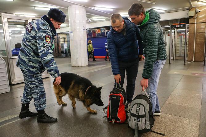 Сотрудник полиции с собакой проводит досмотр личных вещей пассажиров метро на станции «Китай-город»