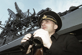 Морской офицер корабля Северного флота наблюдает в бинокль за зоной подъема атомной подводной лодки «Курск», 2001 год