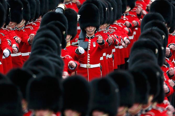 Гвардейцы маршируют мимо Букингемского дворца перед церемонией выноса знамени