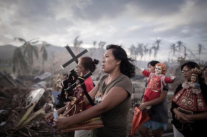 Фотограф агентства France-Presse Филиппе Лопез из Франции завоевал первое место в категории «Горячие новости» со снимком ритуальной процессии в Толосе, Филиппины, в которой приняли участие выжившие в тайфуне «Хайян»