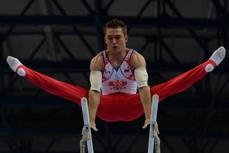 Российский гимнаст Давид Белявский выполняет упражнение на брусьях