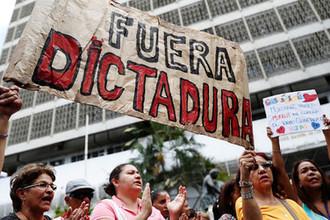 Сторонники лидера оппозиции Венесуэлы Хуана Гуайдо с плакатом «Конец диктатуре» во время митинга против президента Николаса Мадуро на улице Каракаса, 30 января 2019 года