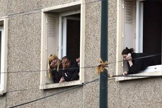 Жители соседних домов наблюдают за действиями полиции, осаждающей квартиру предполагаемого убийцы