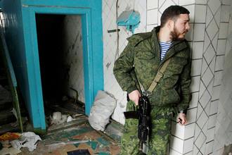 Ополченец самопровозглашенной Донецкой народной республики во время осмотра поврежденного жилого дома в Донецке, февраль 2017 года