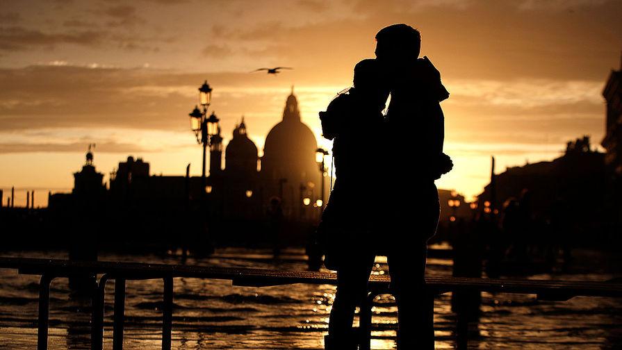 Пара наблюдает закат в затопленной (площадь Сан-Марко ушла под воду более чем на один метр) Венеции, 17 ноября 2019 года