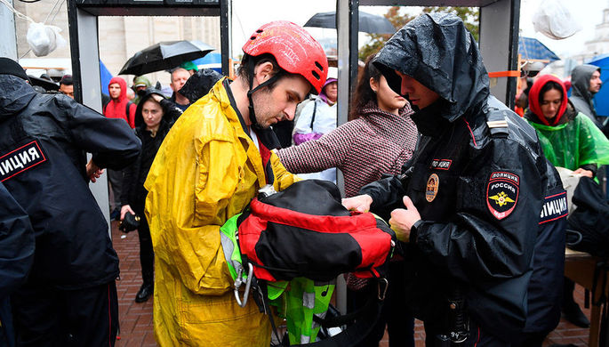 Сотрудник полиции досматривает вещи участника митинга в поддержку незарегистрированных кандидатов в Мосгордуму на проспекте Академика Сахарова в Москве