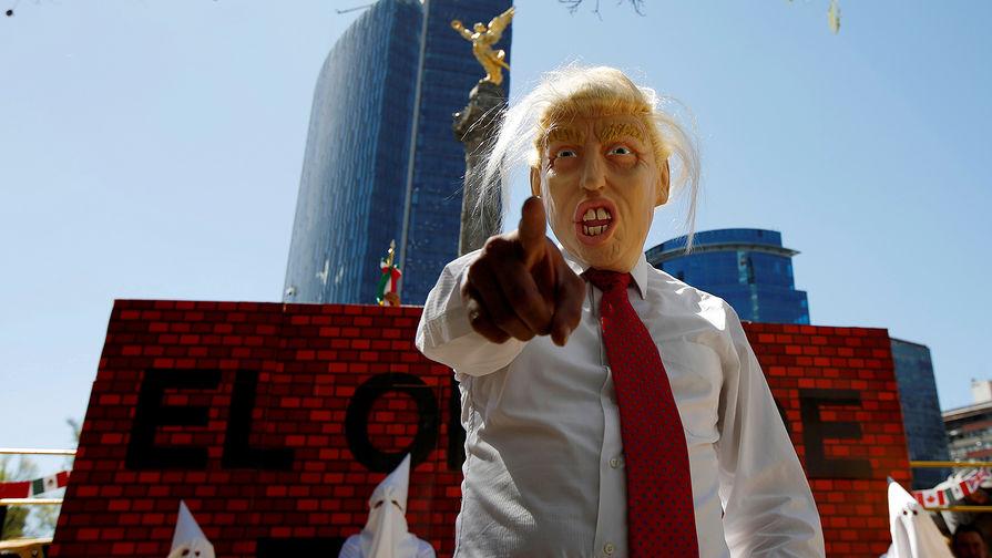 Актеры в костюмах президента США Дональда Трампа и членов ку-клукс-клана во время протестной акции в...