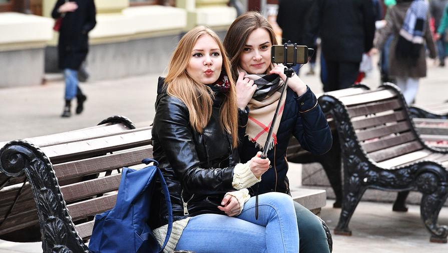 Девушки фотографируются на Никольской улице в Москве