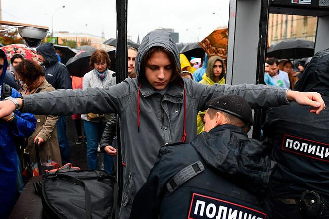 Cотрудник полиции досматривает участника митинга в поддержку незарегистрированных кандидатов в Мосгордуму на проспекте Академика Сахарова в Москве