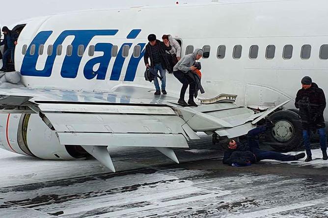 Пассажиры выбираются из самолета, совершившего жесткую посадку в аэропорту Усинска, 9 февраля 2020 года