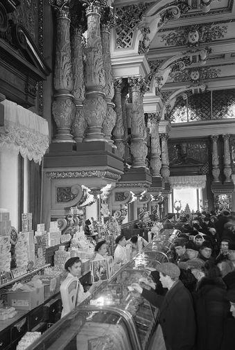 В 1944-м в магазине открылся коммерческий отдел, где можно было приобрести товары без карточек. На фото: продажа колбасных изделий в Елисеевском магазине, 1956 год
