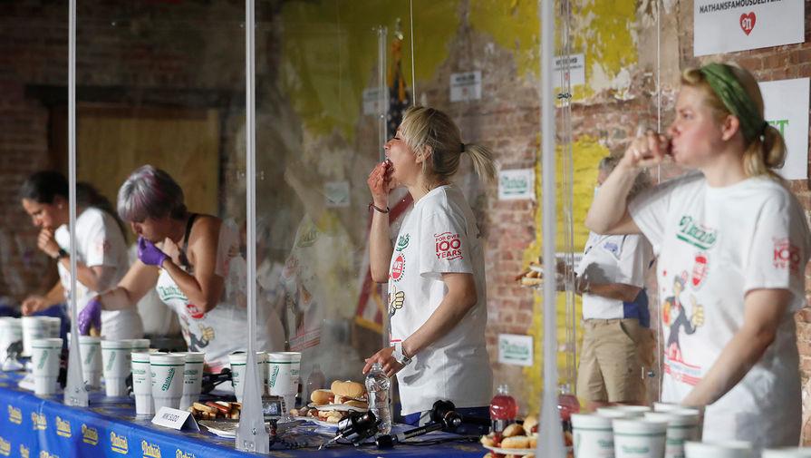 Американка Мики Судо (вторая справа) во время конкурса по поеданию хот-догов, 4 июля 2020 года