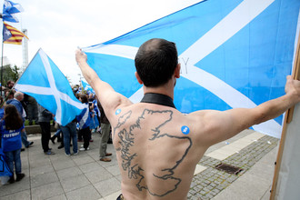 Сторонник независимости Шотландии с татуировкой в виде Шотландии на митинге в Глазго