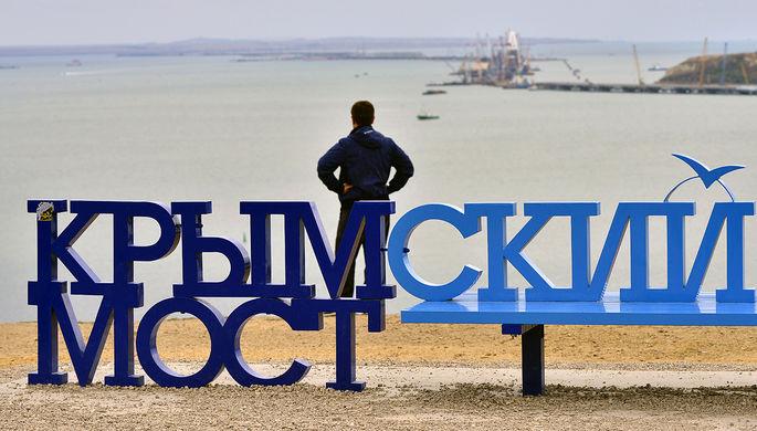 Скамейка «Крымский мост» на фоне железнодорожной арки моста через Керченский пролив...