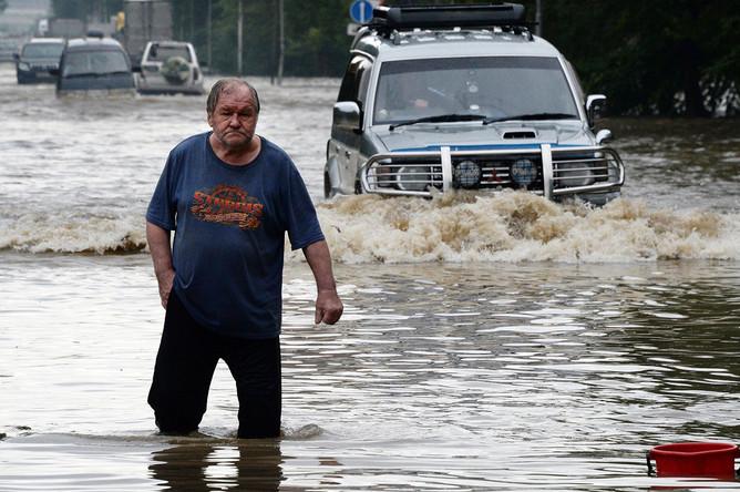 Мужчина и автомобили на затопленной улице Уссурийска