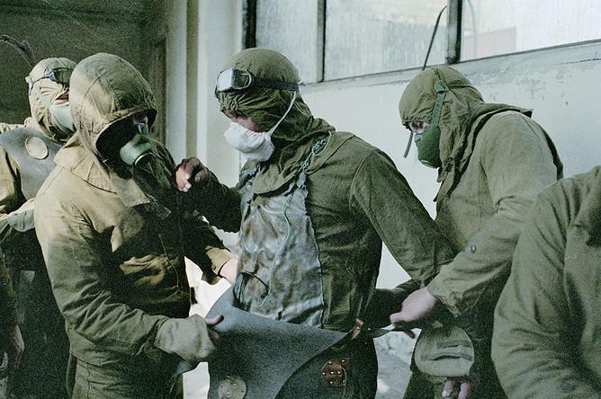 Люди, занимающиеся расчисткой кровли поврежденного реактора, надевают защитные костюмы