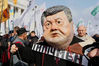 Человек в маске с лицом президента Украины Петра Порошенко во время протестной акции сторонников экс-главы Одесской области Михаила Саакашвили около здания Рады в Киеве, 17 октября 2017 года